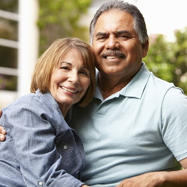 A mature couple smiling and embracing because of our dental crowns that are offered as part of our Hemet dental services.