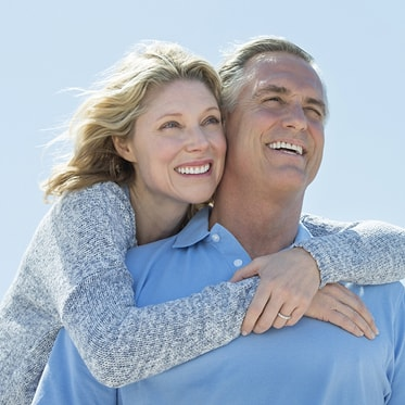 A mature couple hugging andsmiling becasue they replaced their missing teeth with dental implants which is offered as part of our Hemet dental services.
