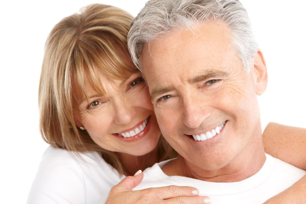 A couple smiling with beautiful dental implants