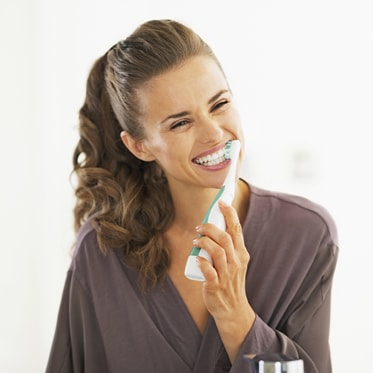 A woman happily brushing her teeth to show that we offer Hygiene & Gum Treatment as part of our Hemet dental services.