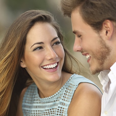A pretty woman with long hair smiling at her boyfriend because of inlays and onlays, which are offered as part of our Hemet dental services, restored her smile.